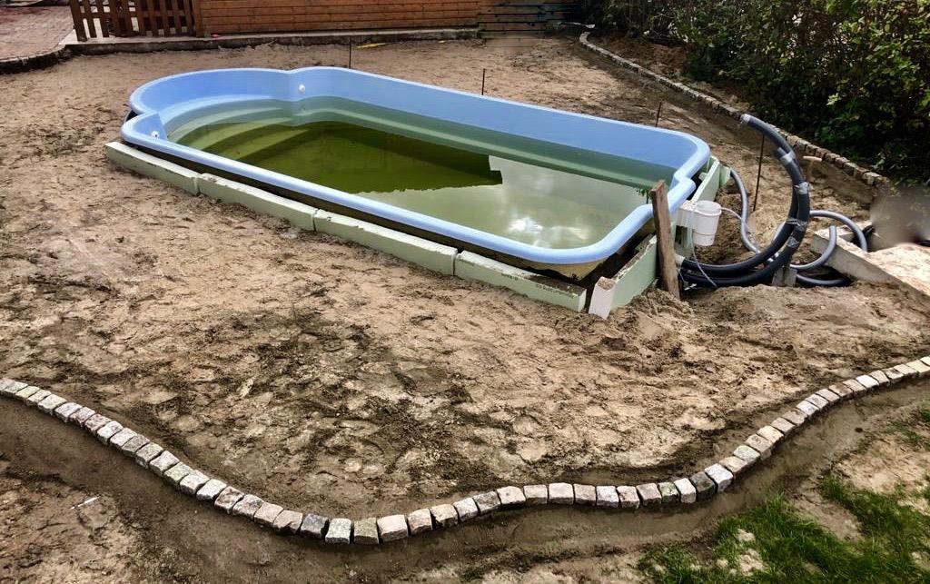 Hier ist der Garten Pool bereits eingelassen und die Randsteine für die Pflasterung gesetzt